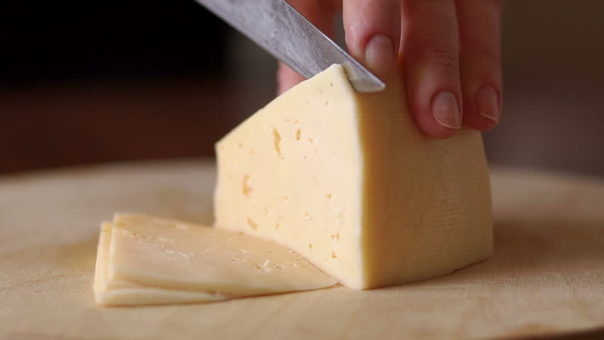 Close-up of female cook or housewife cutting cheese with a knife, slow motion.