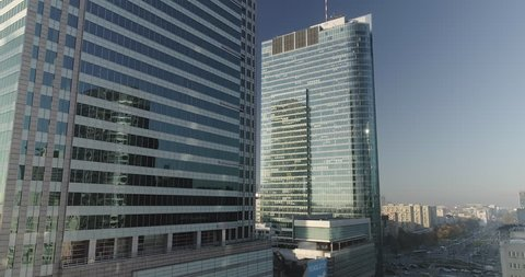 Drone footage of a side movement between skyscrapers and glass office buildings in Warsaw. Sunny summer day in the Polish capital city center.