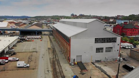 A slow forward moving aerial establishing shot of a typical warehouse or factory in Pittsburgh's Strip District neighborhood.