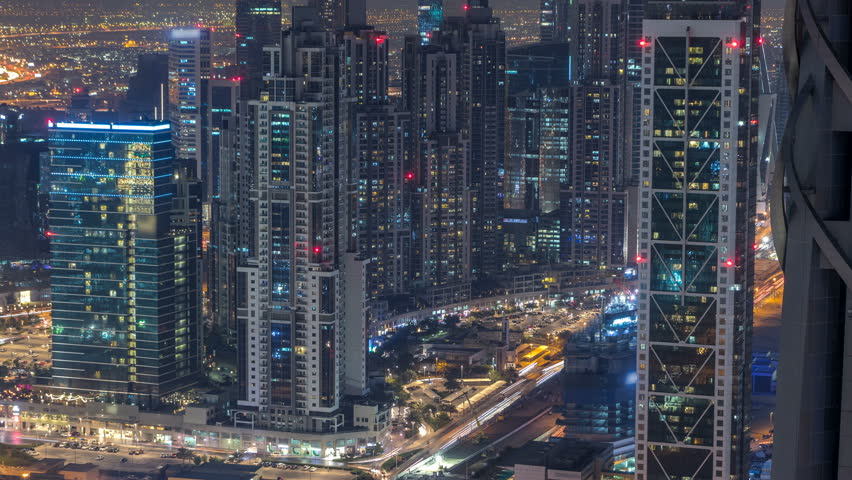 Dubai Downtown skyscrapers night timelapse modern towers view from the top in Dubai, United Arab Emirates. Traffic on the road near business bay