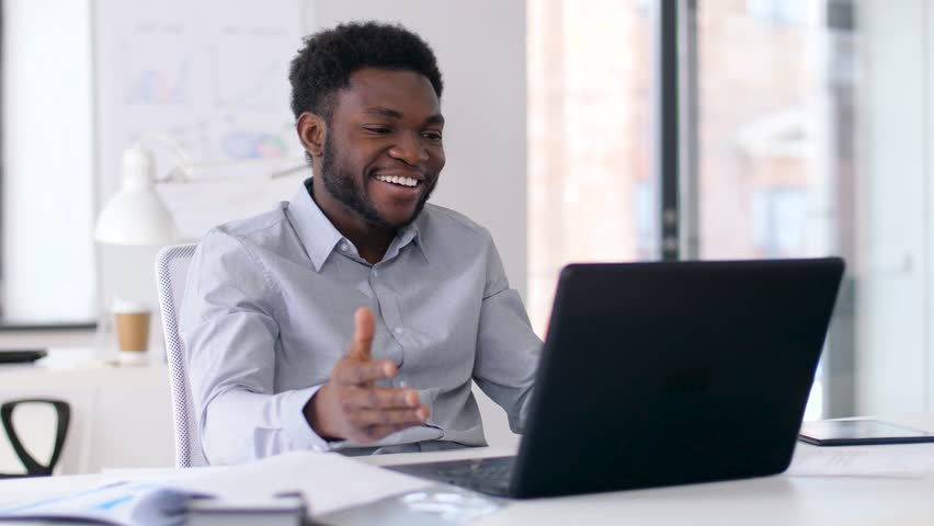 Business, technology and communication concept - happy smiling african american businessman having video chat on laptop computer at office | Shutterstock HD Video #1010703950