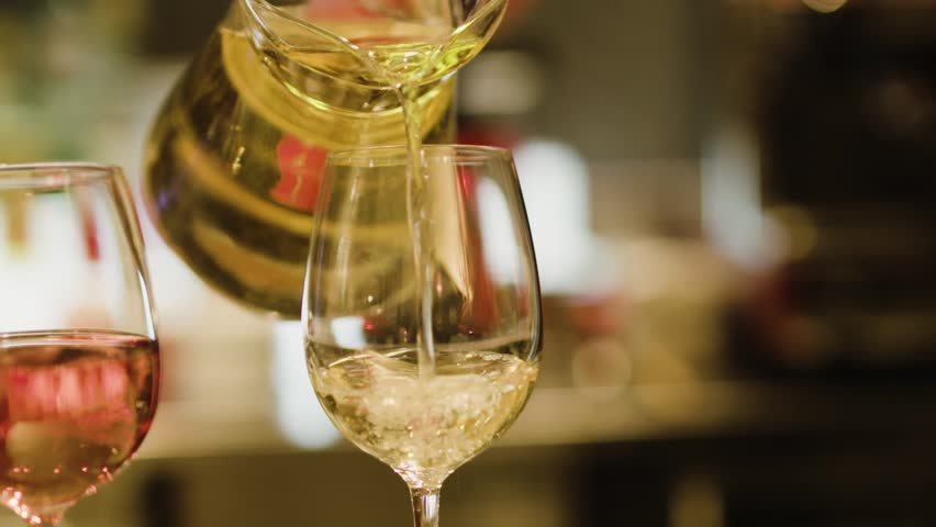 Pouring sparkling wine in champagne glasses in slow motion. Reception, gala, event, celebration, night out