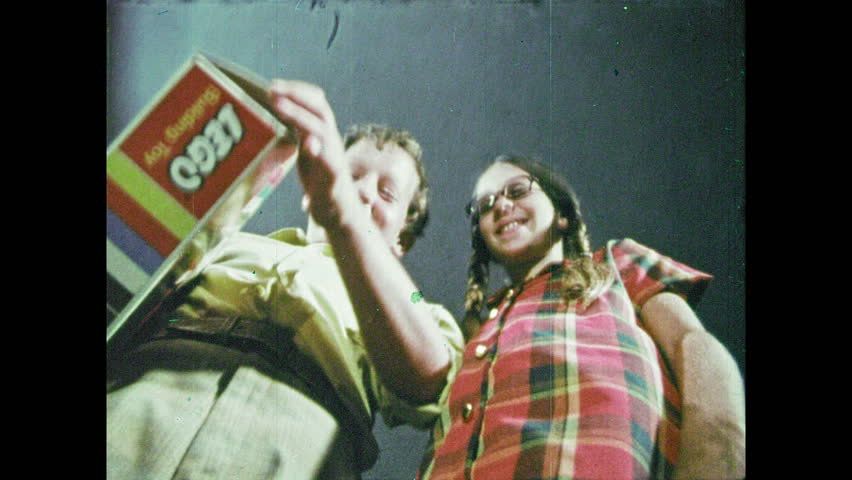 1970s: Boy and girl open box and pour Legos out. Pills fall from the sky. Boy and girl pour Legos from box.