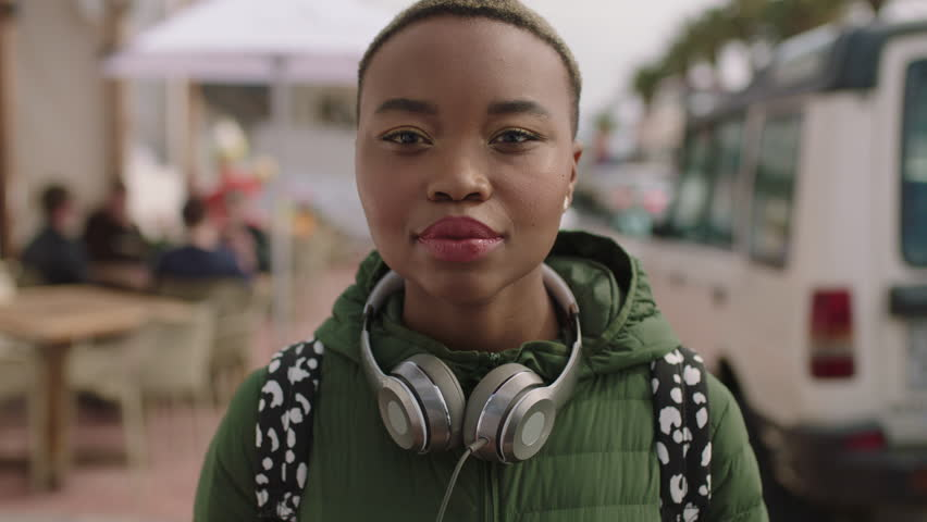 Portrait of young beautiful african american woman looking serious wearing headphones beachfront background | Shutterstock HD Video #1010716520