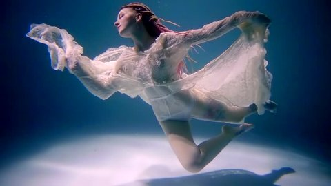 Stunning young model is floating in pose underwater.