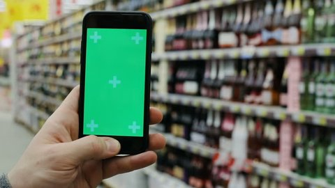 human hand using smart phone cellphone on blur background in supermarket space alcohol department online shopping app checking price tapping chromakey mockup swapping internet connecting wifi