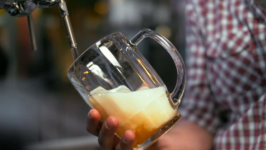 A bartender man in a plaid shirt pours cold unfiltered light beer into a transparent beer mug. Ireland. Super Slow Motion Shot