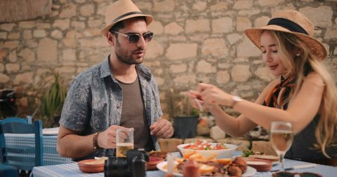 Young tourists on Greek island holidays eating Mediterranean food at traditional rustic restaurant