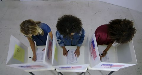LS Wide overhead view three young women with Hispanic/Latina woman looking up and thinking while completing ballots at voting booths in polling station. Locked off, slow motion 4K 60fps