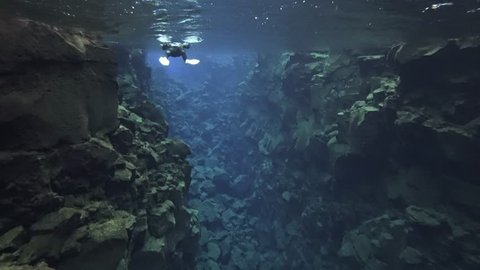 Snorkeling and diving in the clear, ice cold water in Silfra fissure in Iceland. Blue underwater lava.