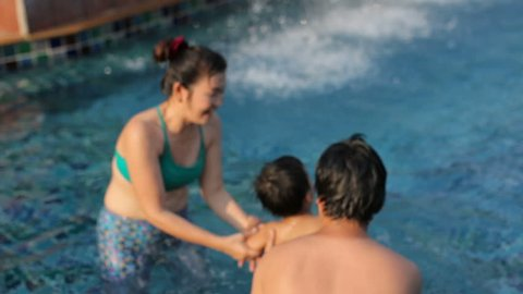 asian family playing with happiness relaxing in water pool