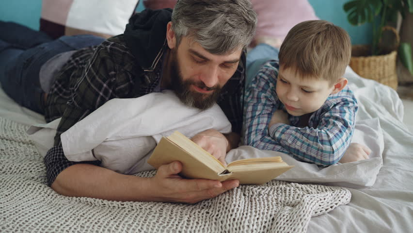 Loving parent bearded man is reading interesting book to his curious little son on double bed at home. Parenthood, happy people, love and family concept.