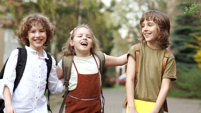 Three schoolchildren, boys and girl go to school. Behind their shoulders are school knapsacks. The girl is hugging the boys cheerfully. school friendship. Back to school | Shutterstock HD Video #1010833250