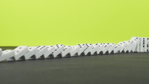 Domino effect - a series of dominoes falling down the chain on yellow colorful background