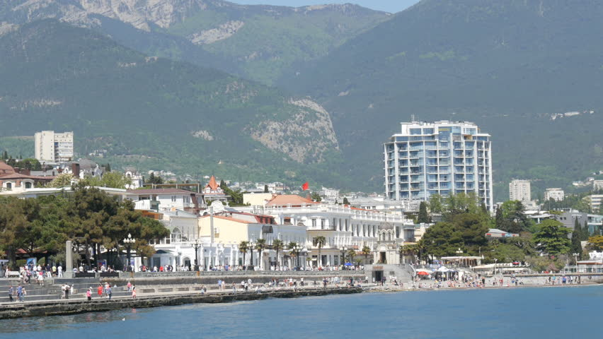 Yalta, Crimea - May 1, 2018: Embankment of the sea city, on which people walk. A sea city in the mountains