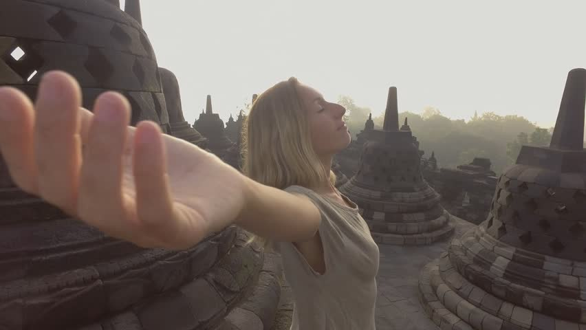 4K resolution video of travel girl embracing sunrise at Borobudur temple, Indonesia . People discovery Asia concept