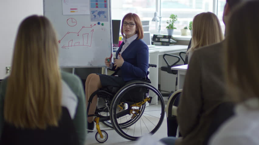 Tilt up of female business coach sitting in wheelchair and explaining bar graph on flipchart to group of office workers