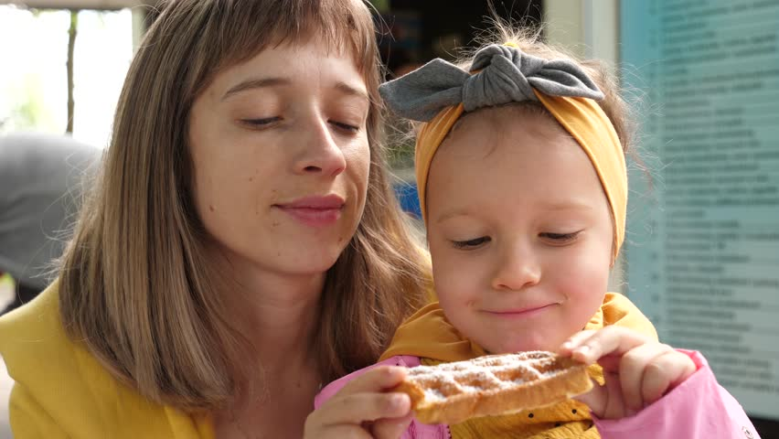 Cute woman and little child girl portrait while eating Belgian waffle, mother kiss daughter cheek