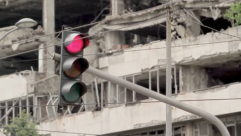 Traffic light on the background of the destroyed building of NATO bombing in Belgrade.