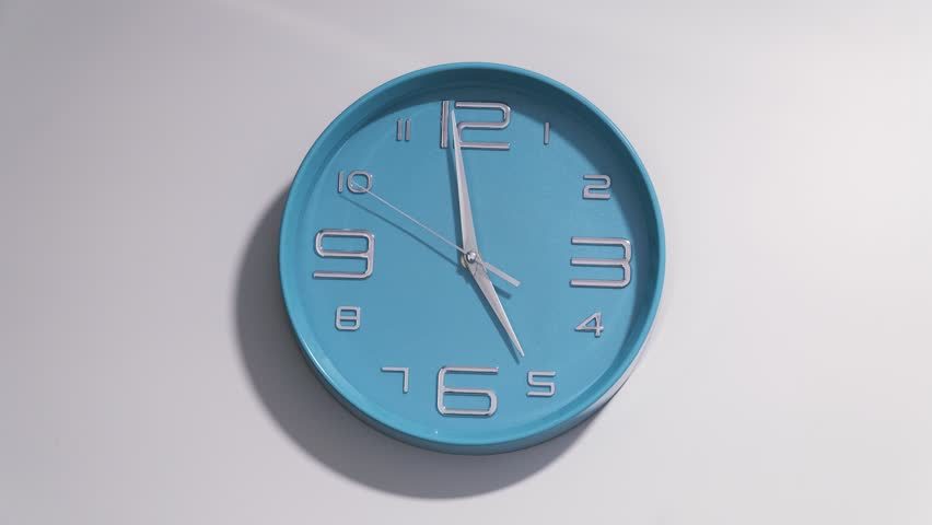 Timelapse of a blue clock on a white background. The clock starts ticking at 5 and ends at 12.