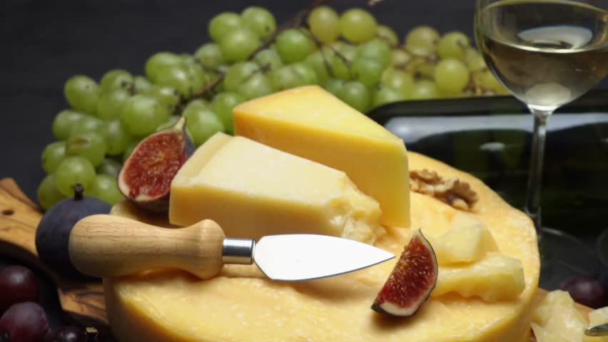 Video Whole round Head of parmesan or parmigiano hard cheese, grapes and wine