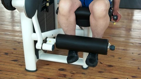 Close up senior man training legs at gym. Man doing exercise with weightlifting machine in fitness center. Muscle and fitness.