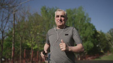 Senior seventy years old man jogging in the city