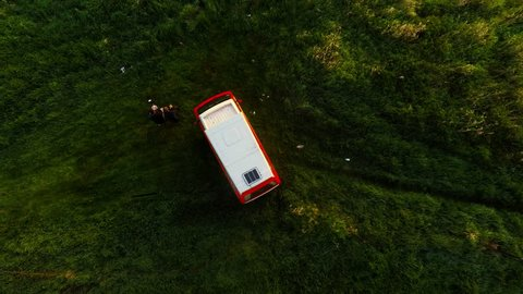 MILSKO, LUBUSKIE, POLAND - APRIL 12, 2018: Classic Orange and white Volkswagen camper van parked in green meadows. Drone footage looking directly down from above and ascending.