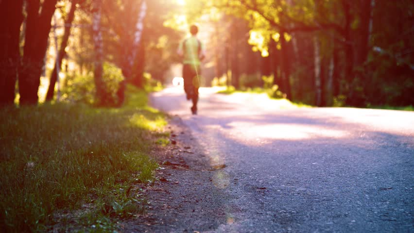 FHD sport man running at new asphalt road outdoor. Sunrise or sunset in rural city park. Green tree forest and sun rays on horizon. | Shutterstock HD Video #1010945270