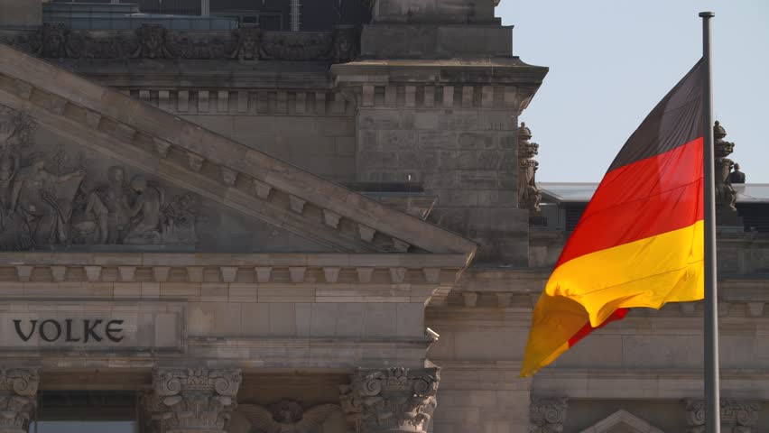 German national flag in front of the Reichstag building in Berlin.
