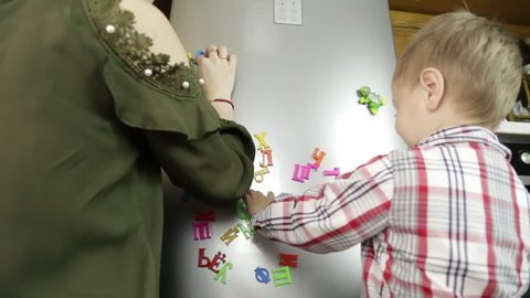young babysitter with a little boy learning the alphabet on magnets