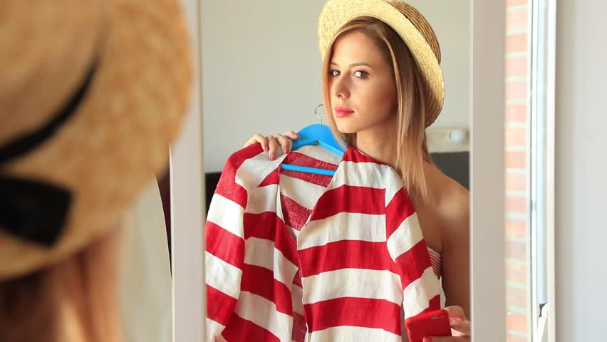 Young girl dressing up near a mirror. Choosing a clothes for vacation and making a selfie