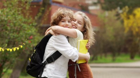 Girl and boy, schoolchildren embrace joyfully. School friendship, first love. Curly, elegant children. Back to school. Teenage couple