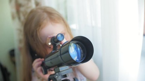 A little girl looks through a telescope from the window of her house 4k