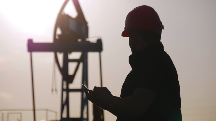 Oil drill, field pump jack silhouette with setting sun and worker. Oil field, the oil workers are working.
