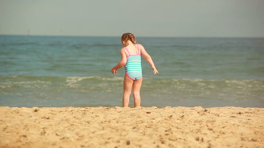 Two girls and a little boy playing with sand on the beach | Shutterstock HD Video #1011065030