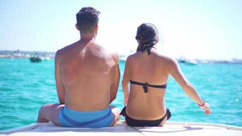 Beautiful young couple relaxed in yatch, Asian girl and strong man in a boat with the perfect sea