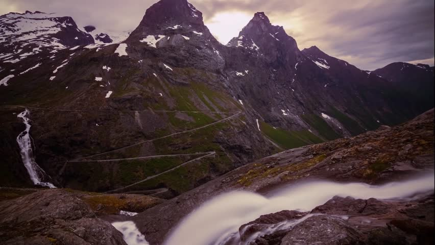 scenic timelapse clouds floating over rocky norway mountains with hairpin bends of Trollstigen mountain pass and waterfall in the foreground