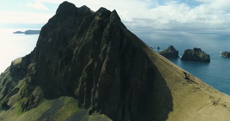 Aerial: Epic mountains in the Atlantic ocean. Stunning cliffs. Sunny day. Iceland.