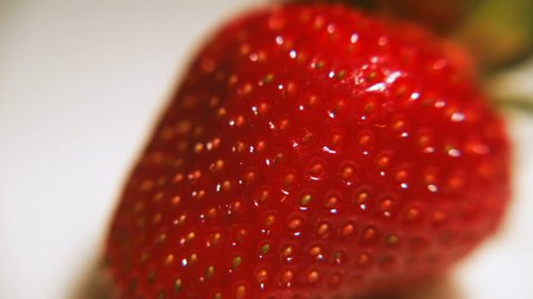 Ripe fragrant strawberry rotates on a white background. The time of the summer fruits.