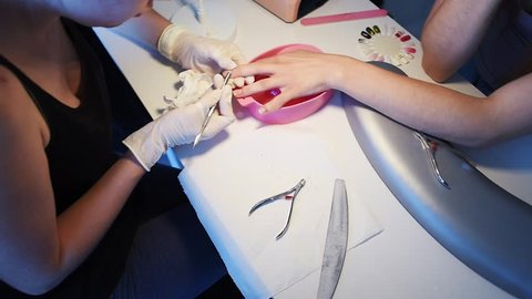 Manicurist in disposable gloves using cuticle pusher for pushing cuticles on client's little finger. Sample palette with gel polish colors and instruments. Slow motion.