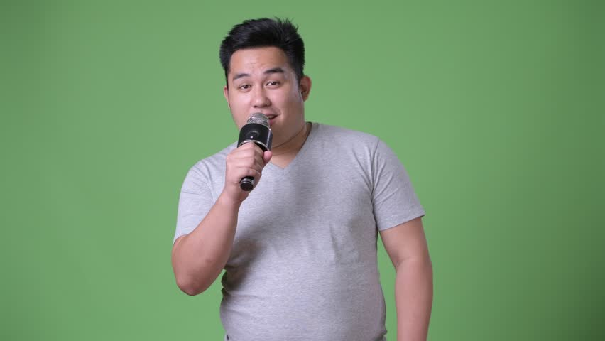 Young handsome overweight Asian man against green background | Shutterstock HD Video #1011177830