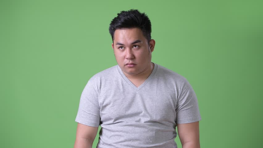 Young handsome overweight Asian man against green background | Shutterstock HD Video #1011178310