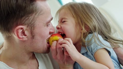 Medium shot of cute little girl and happy father laughing and biting juicy apple