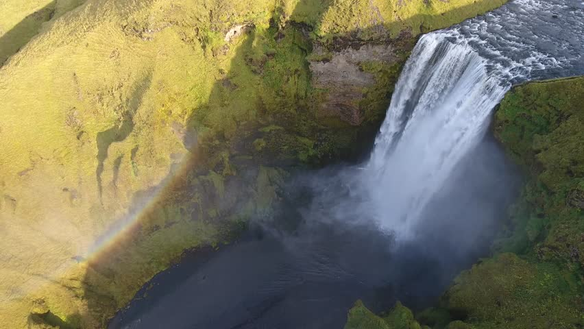 Aerial drone shot flying over the famous Skogafoss waterfall in Iceland. Rainbow sunny day. medium altitude flight