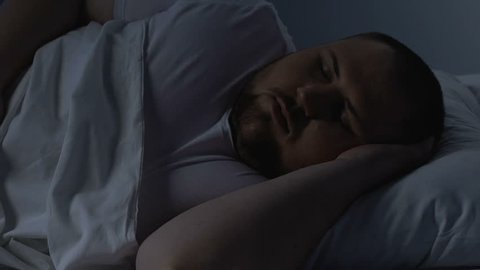 Obese man tossing in bed, suspension of breathing, inhaling problem, apnoe