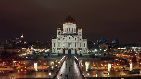 Flying towards the Cathedral of Christ the Savior in Moscow. Bright lights of night city life. City panorama at night.