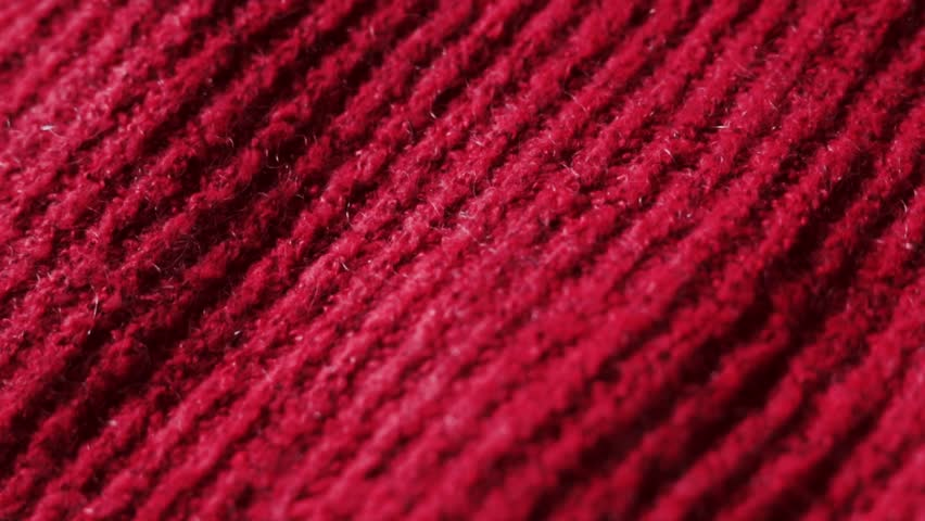 Knitted fabric in cold red color. Can be used as background. Closeup dolly shot.   Shutterstock HD Video #1011239930