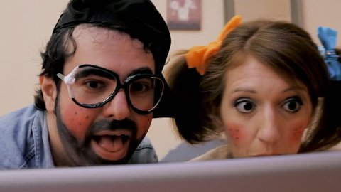 An odd couple (actors in character as kids): a guy and a girl on the bed, watching porn movies on a laptop, feeling the urge to vomit as it's not what they expected. Funny bizarre detail shot.