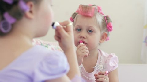 Two little fashionistas in curlers learn to make themselves a make-up. Little girls paint their lips. 4k